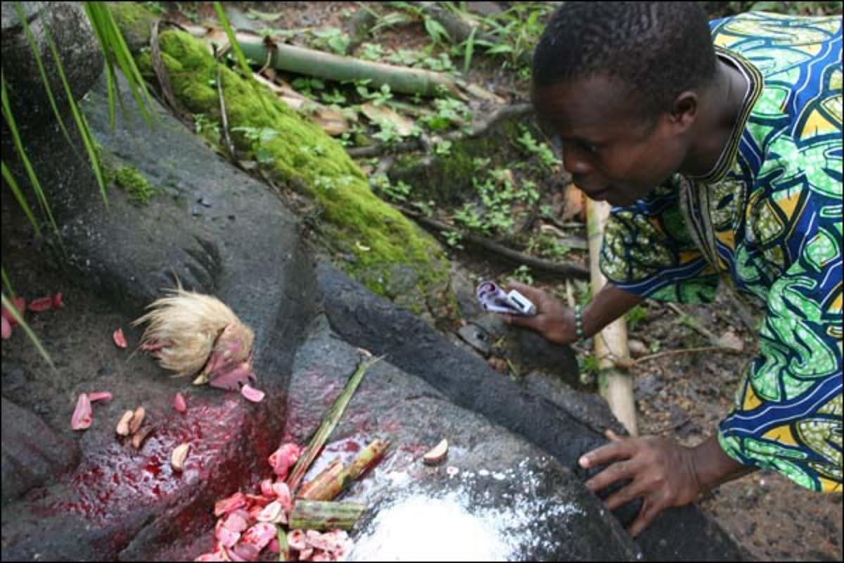 Osun devotee asking for blessings from the River Goddess at Osun Oshogbo Sacred grove