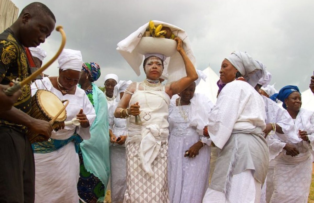 'Arugba' the virgin girl in the middle, chosen to carry the Osun-Osogbo Calabash covered
