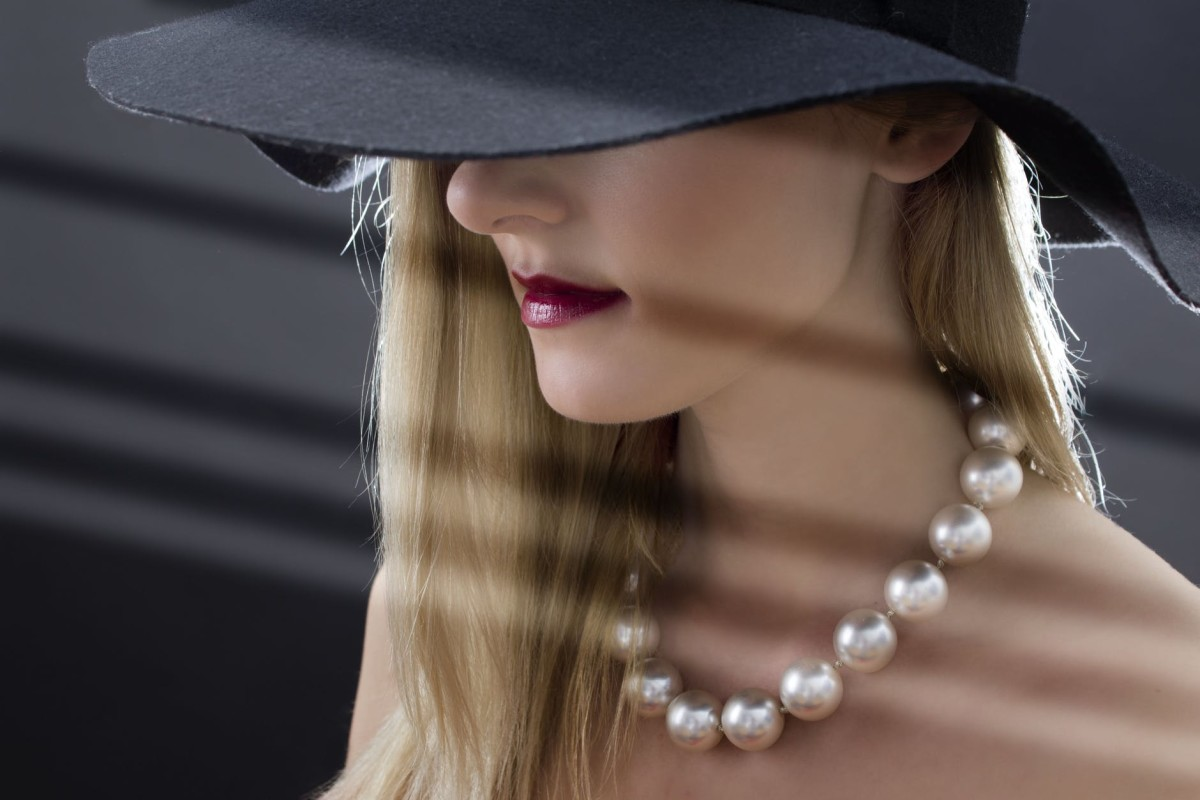 woman wearing a hat and pearls