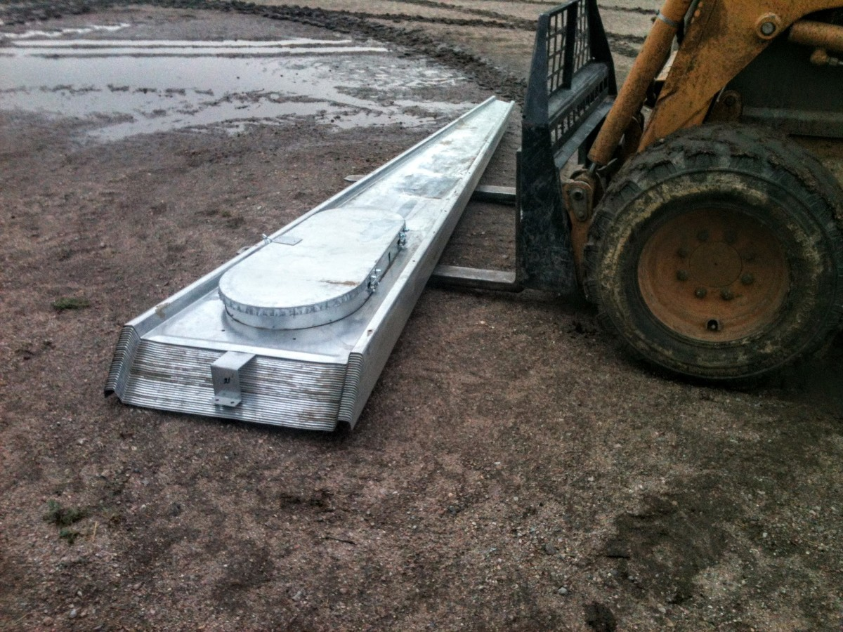 A stack of roof sheets is ready to be used, kept conveniently off the wet ground by the loader forks.