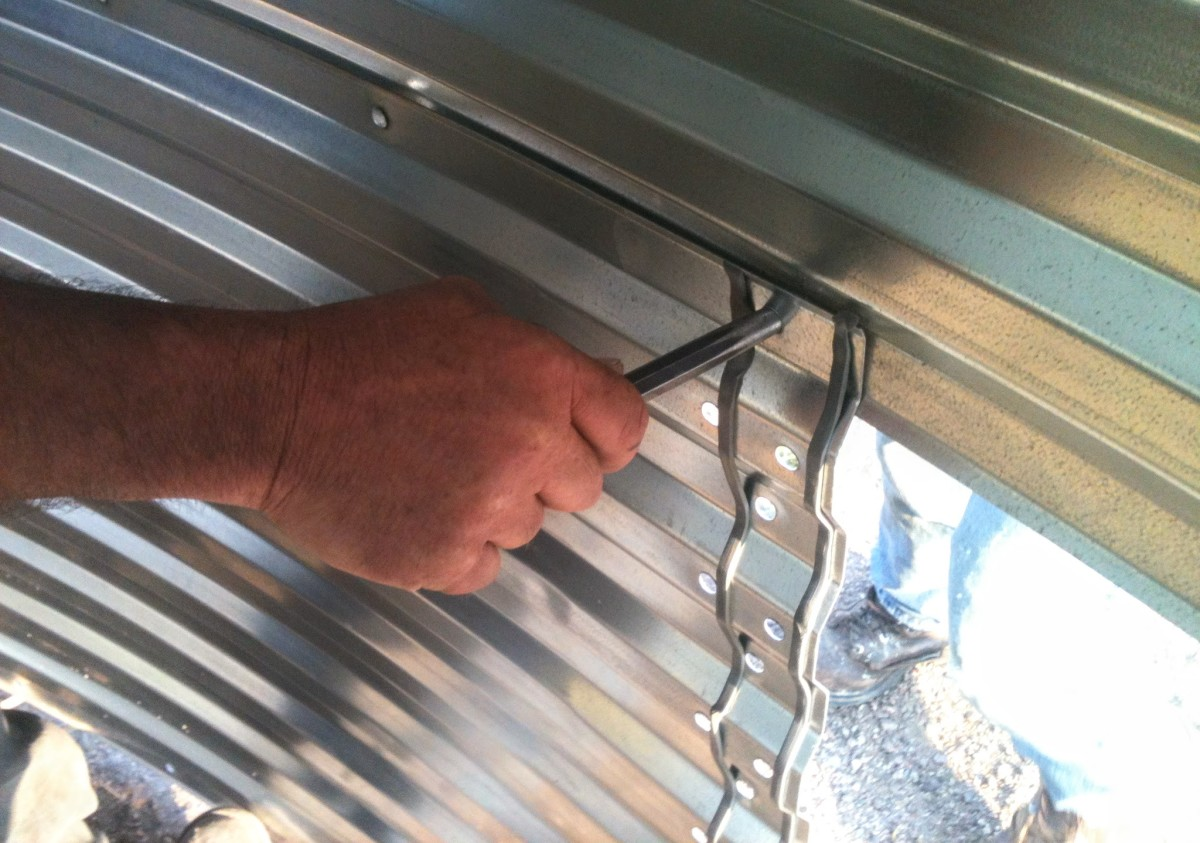 Punches are inserted at eight end of a wall sheet when fitting it into place, both to hold it and to provide leverage to align bolt holes.