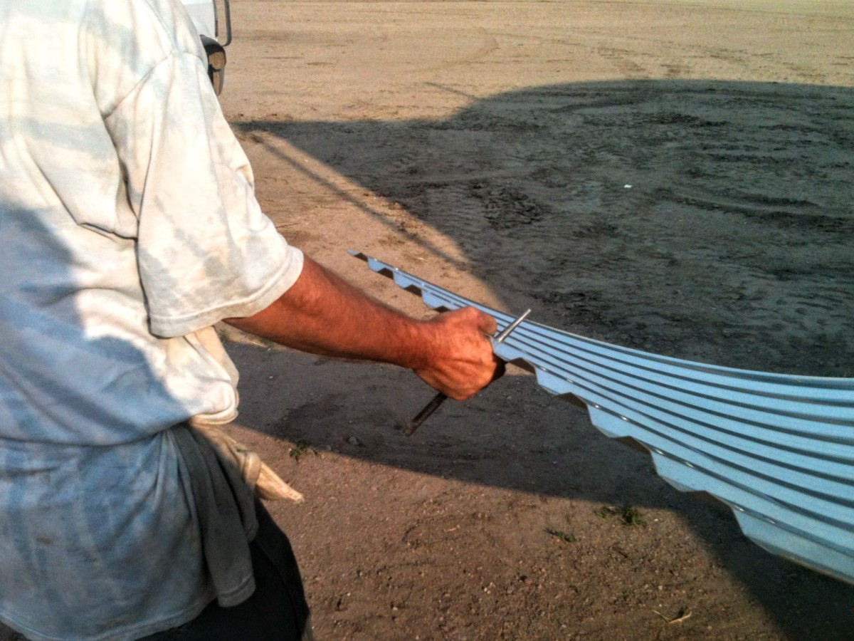 Drift punches are used as handles to drag wall sheets from the pile to the bin perimeter.