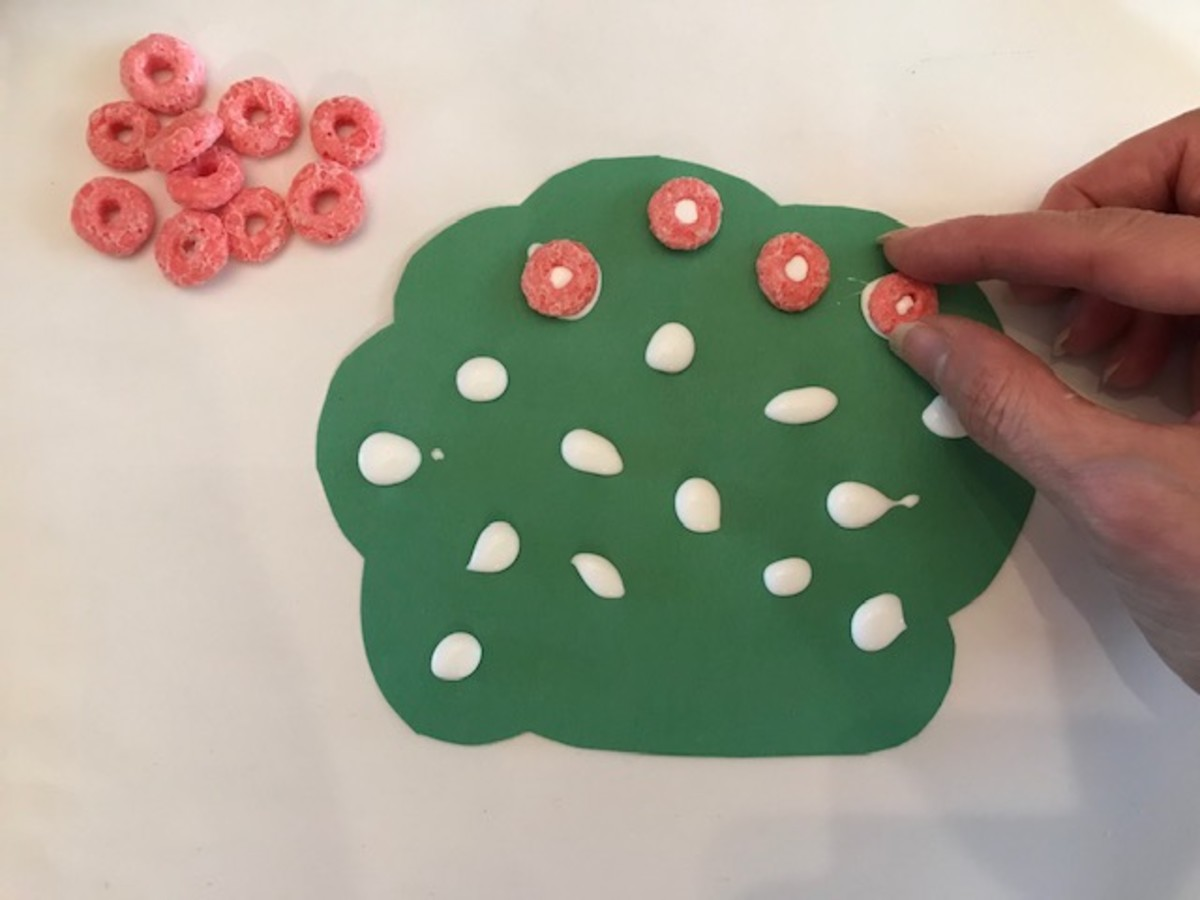 """Gluing the fruit """"froot"""" loops to the tree using tacky glue"""