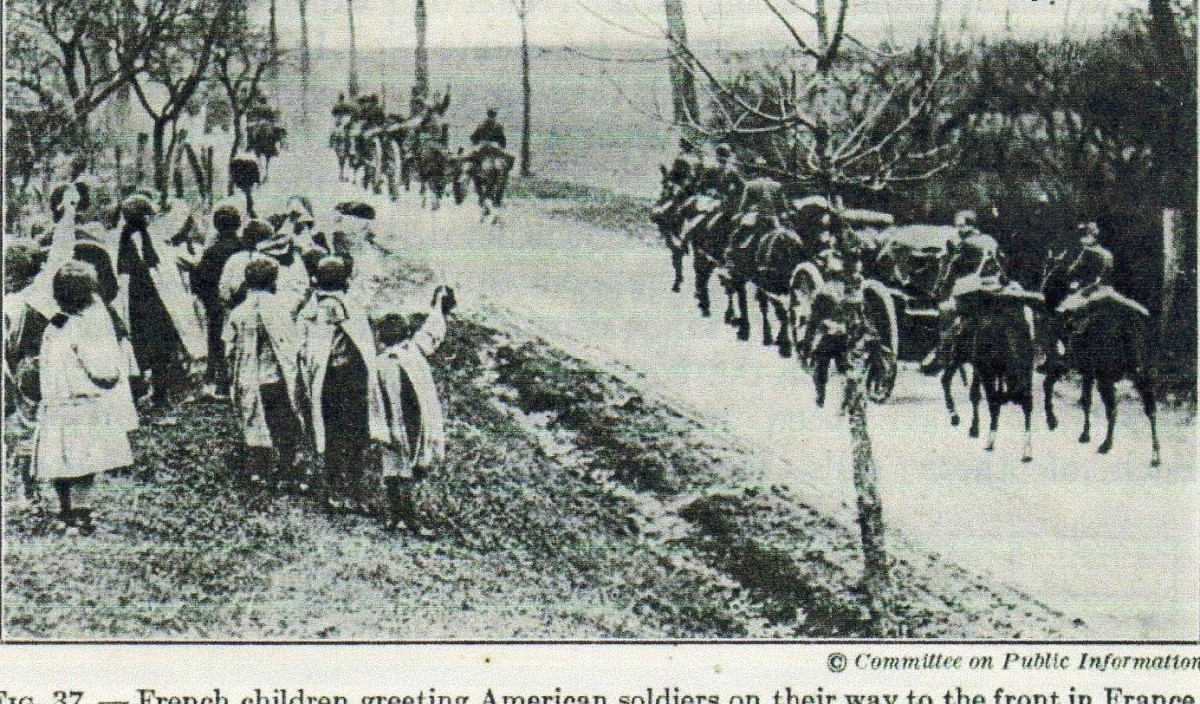 French children salute WW1 troops on their way to the front.