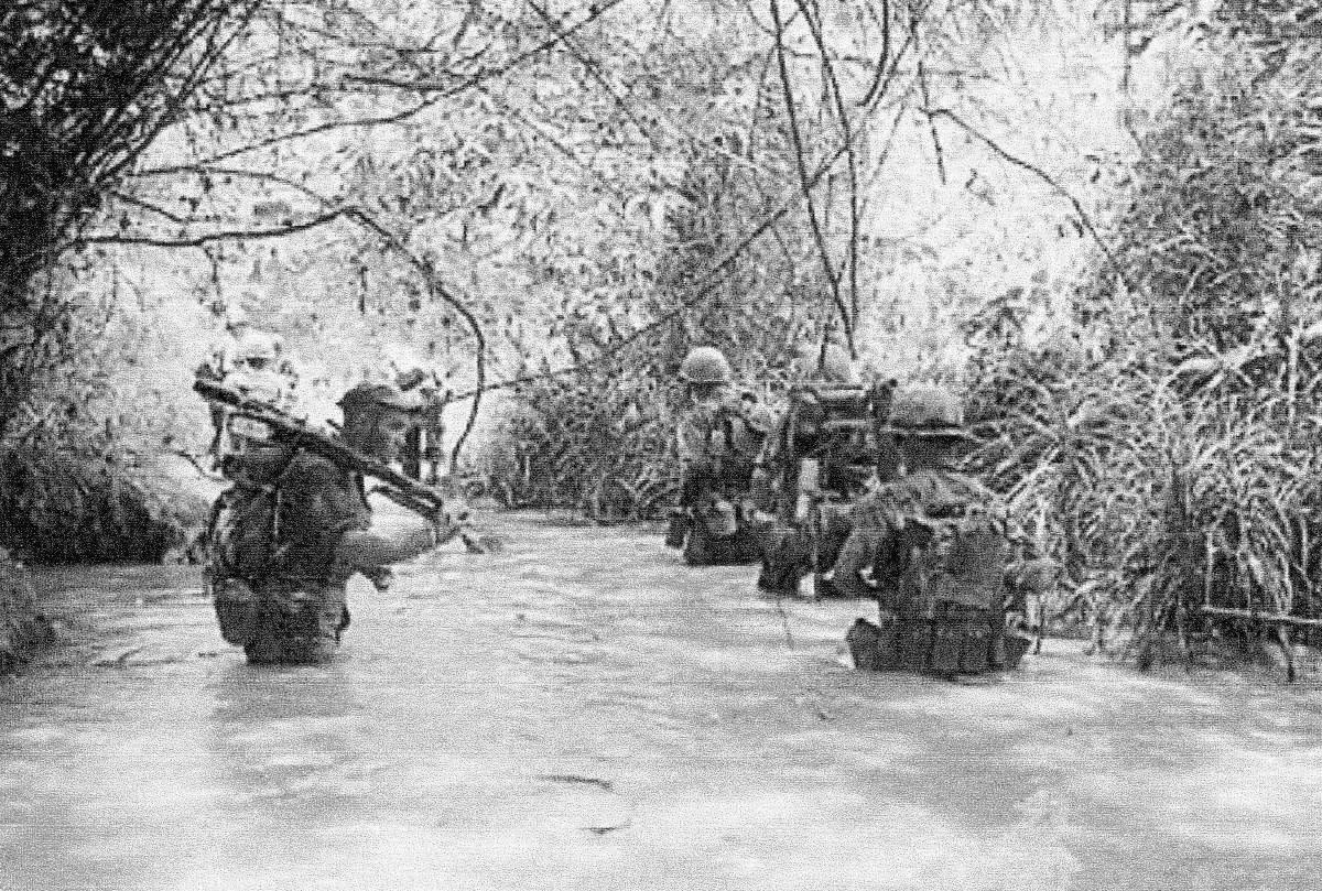 Marines wade through the water.