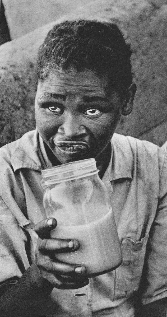 """The poisoning of the beer Botha was talking about has long been an ongoing process in killing-off Africans in south africa. This battered woman is drinking the """"Beer"""" made by the Apartheid regime and displays the slow poisoning  effects  over her."""