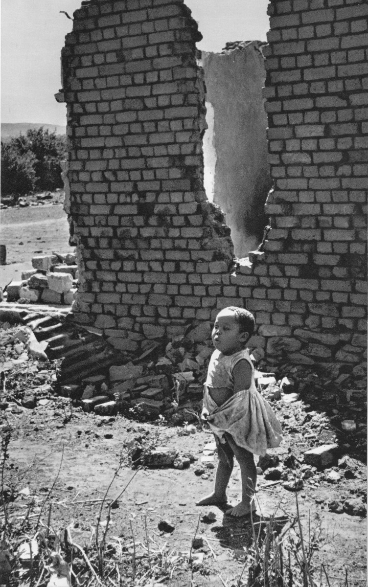 "A child stands next to her home which was bulldozed through 'forced removals' of Africans from places the Apartheid regime dubbed ""Black Spots"""