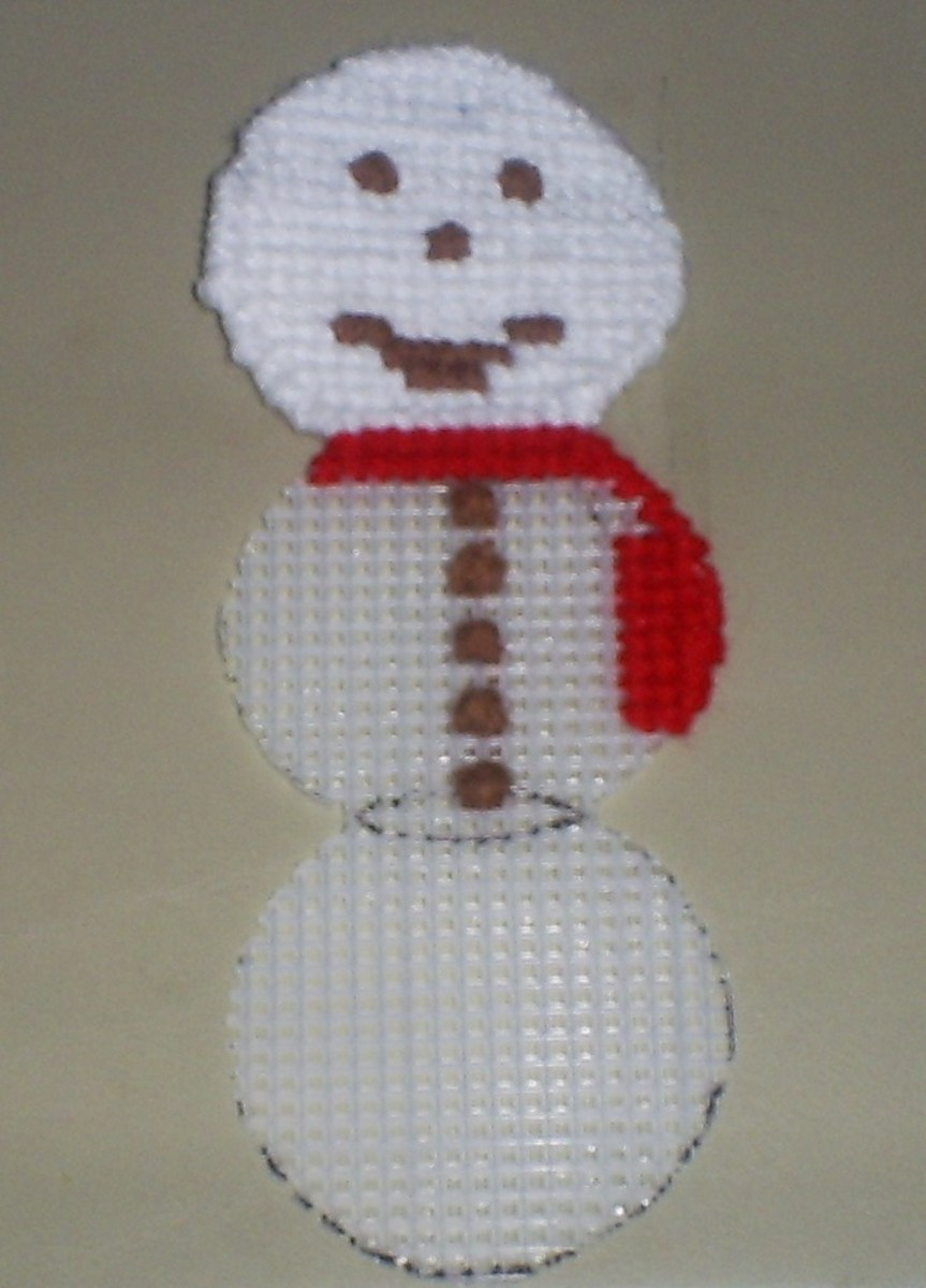 In this stage I have begin to stitch on the snowman's red scarf.