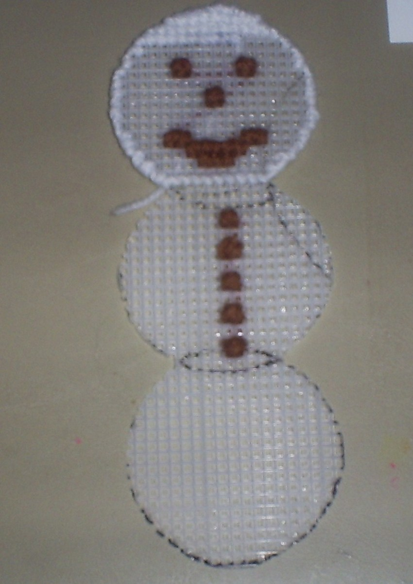 Here I begin stitching the white yarn on to the snowman's head.
