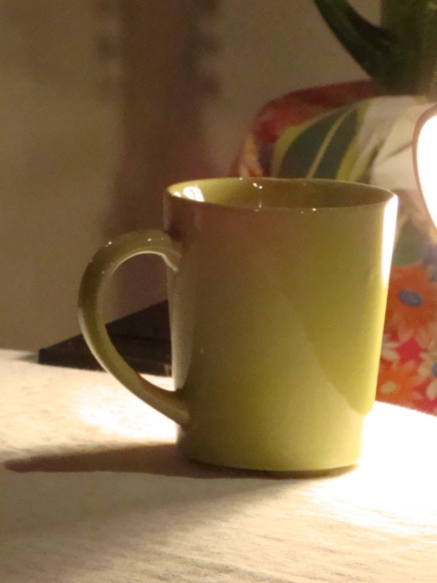 A cup that is lit for a simple still life.