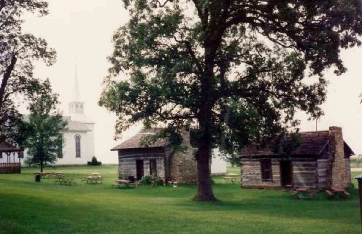 St. Ann's Church in background with a couple of the old cabins in Walnut Grove Pioneer Village