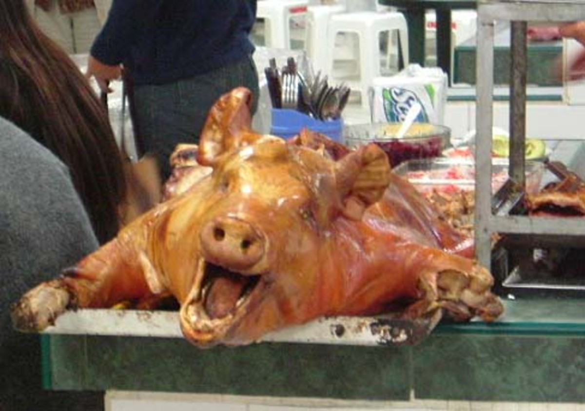 Whole roasted pigs hang from hooks at roadside stands.