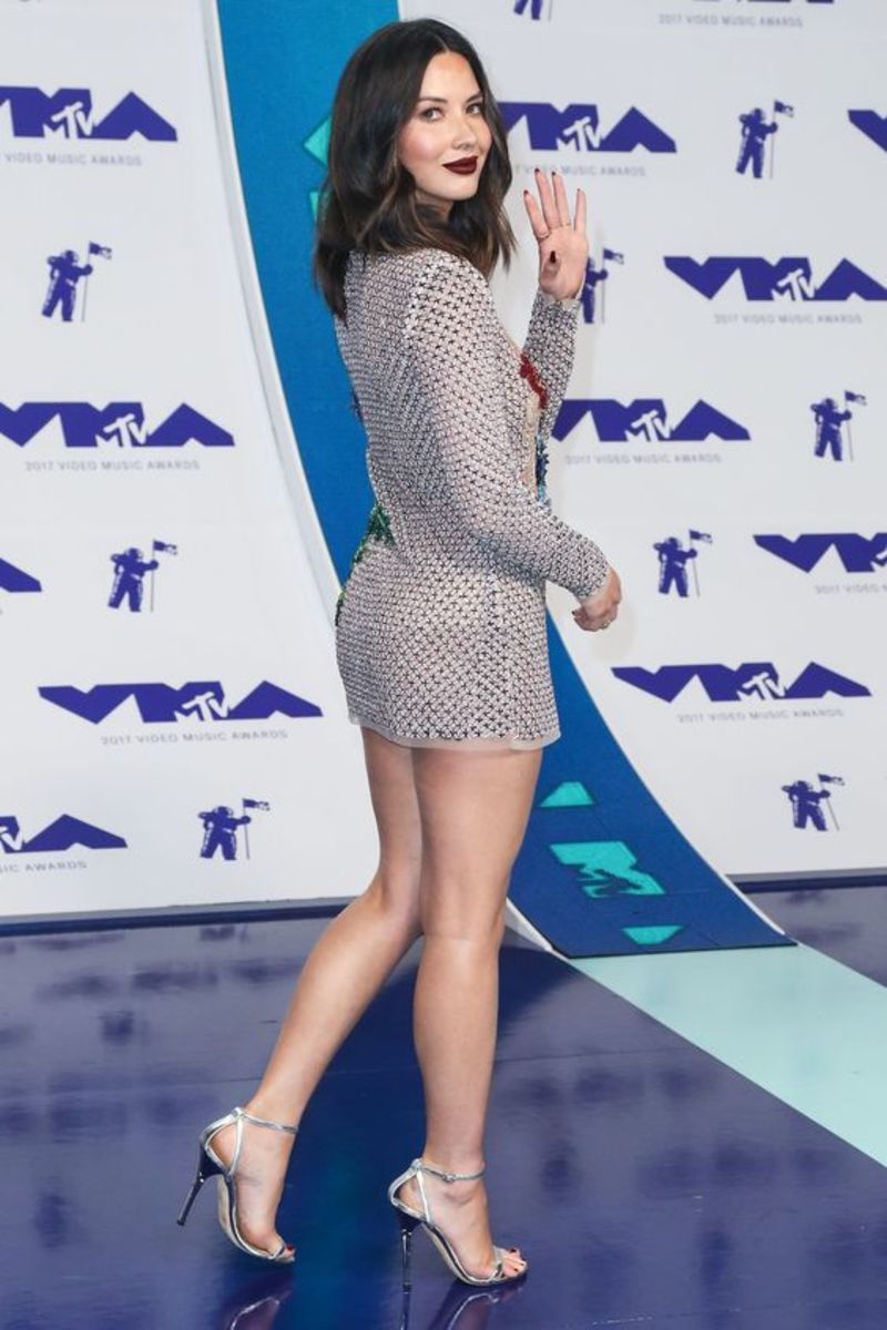Olivia Munn legy in a long sleeve silver mini dress with matching ankle strap high heel sandals