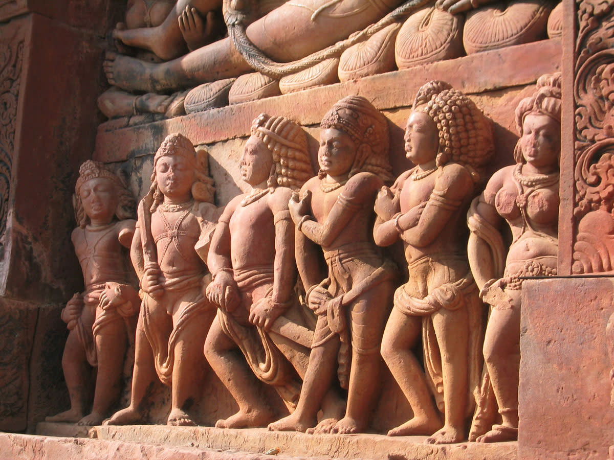 The five Pandava brothers, and Draupadi; they stand below the reclining Vishnu