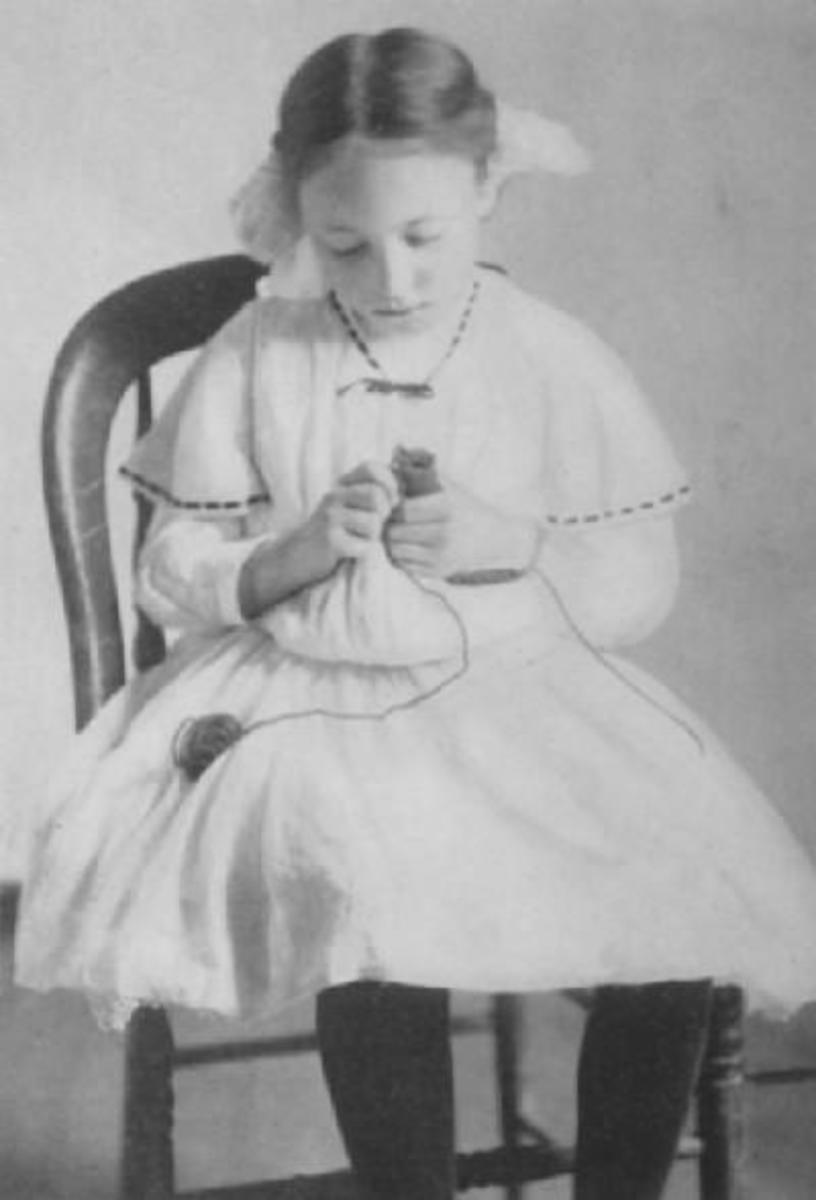 A young girl from the early 1900s knits with a knitting spool. From the book Spool Knitting by Mary A. McCormack