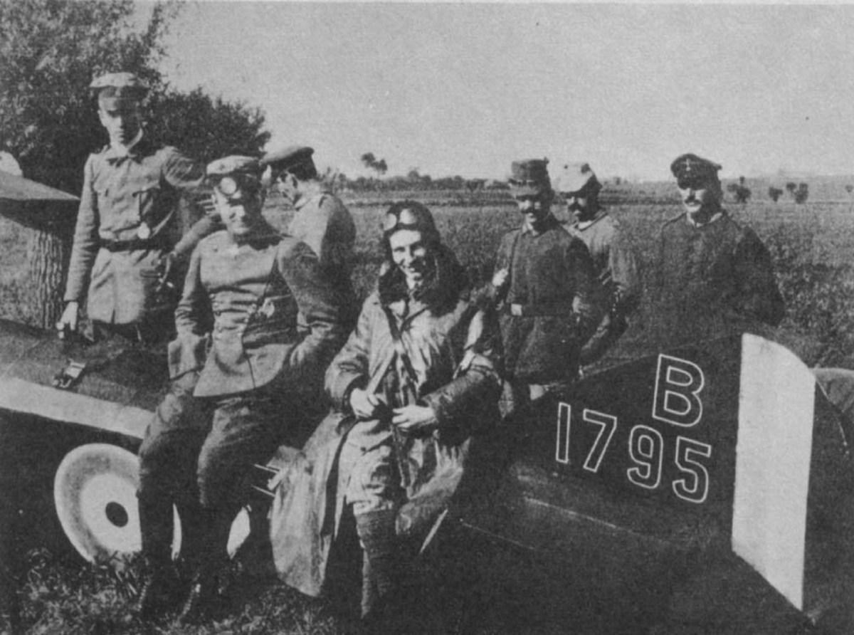 "Manfred von Richthofen (""The Red Baron"") posing beside Anthony Fokker. Both men are sitting on a crashed Allied plane. Richthofen, without goggles, is on the left."