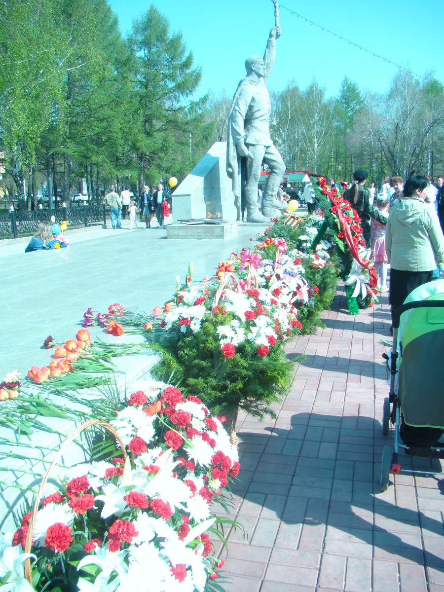 Flowers are laid down by Men , Women and Children during the celebration and holiday of the 9th of May