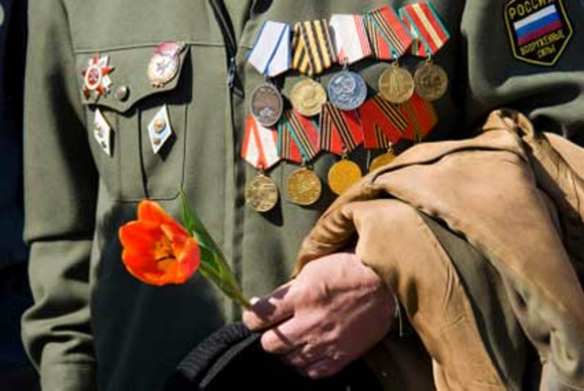 A Russian Wold War II veteran places a poppy on a war memorial site during the Russia celebration of the Patriotic War