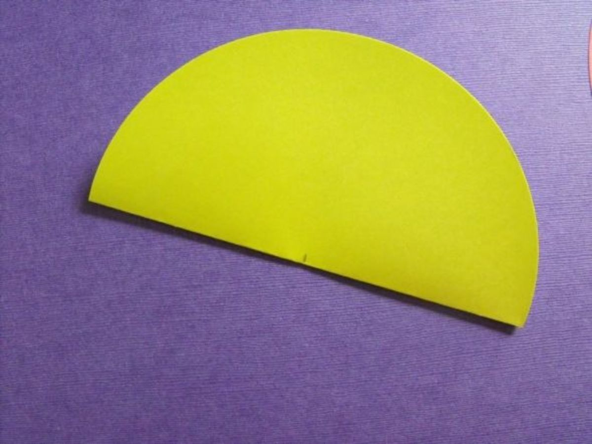 Find the center of the straight edge of the half circle. I fold in half and pinch a small crease. Or use a pencil to mark the center.