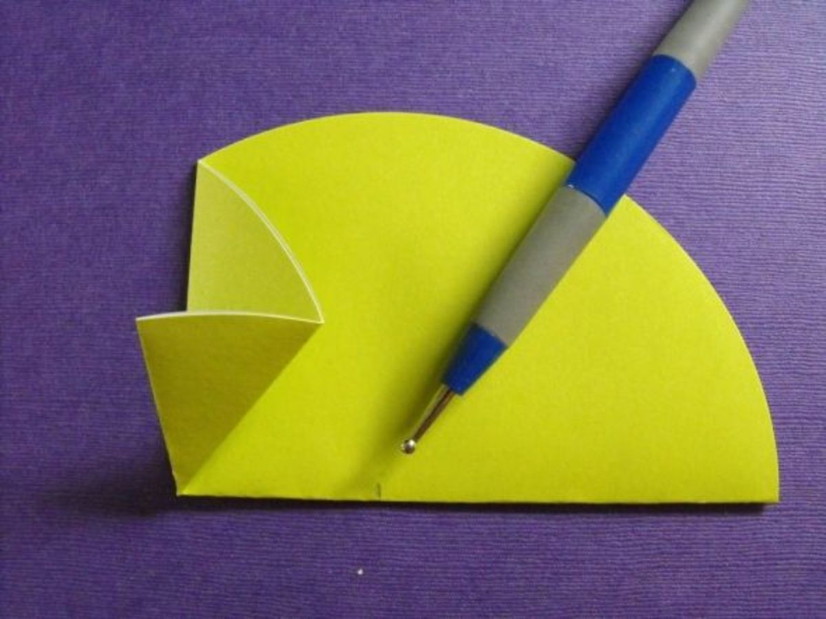 Take the lower tip of the new fold in the center and bring it up to the left to meet the crease along the left side. This will form a cone shape.