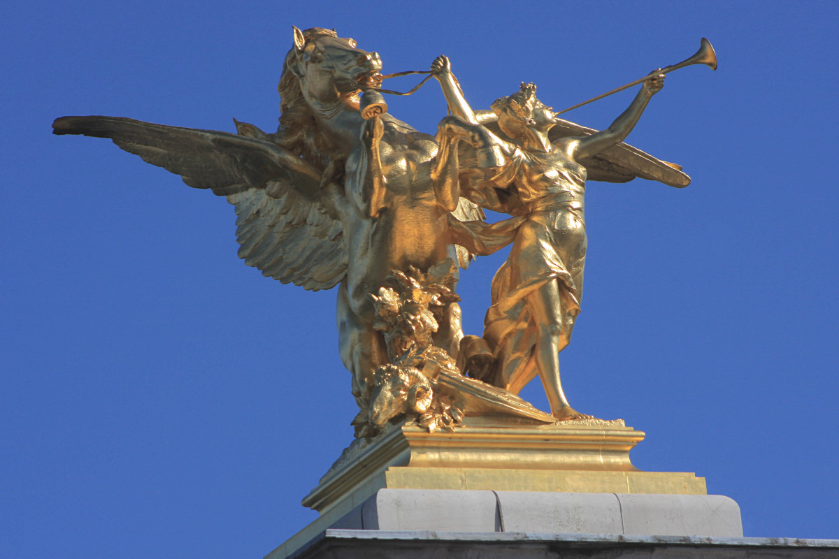 This gilded statue on a 17m (56 ft) high granite plinth, is one of four which guards the entrances to the Pont Alexander III Bridge. The bridge spans the River Seine between the Grand Palais on the north (left) bank, and Les Invalides to the south