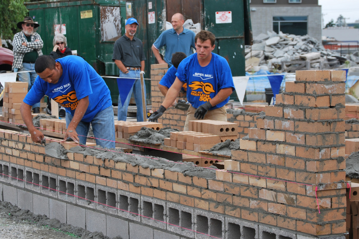 A small gang of bricklayers building a wall with bricks overhand. This practice is not the best practice, because when the building is tall it might become dangerous, but it is safe enough in this case.