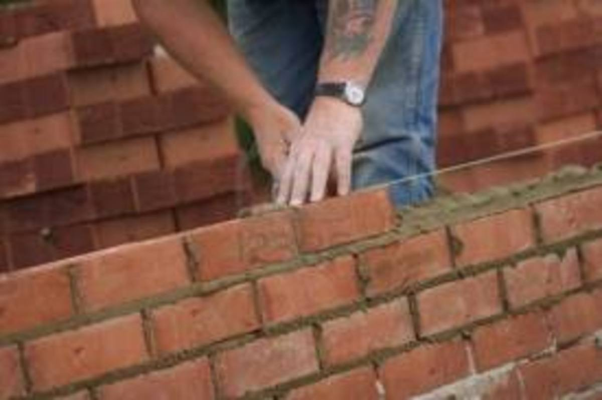 A bricklayer laying bricks on a single wall in stretcher bond. Note how the mortar has been spread and trimmed back and how he lays his bricks following his line.
