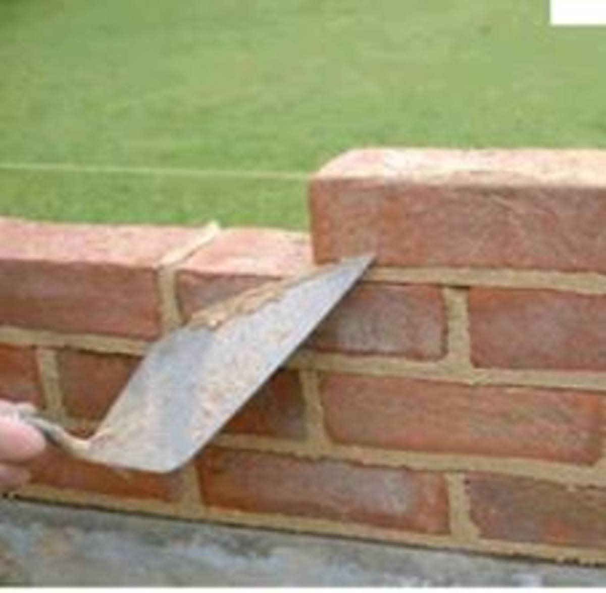This photos shows a bricklayer trowel and how it is used to cut the mortar while laying bricks, you can note also that the top brick has been laid level with the line.