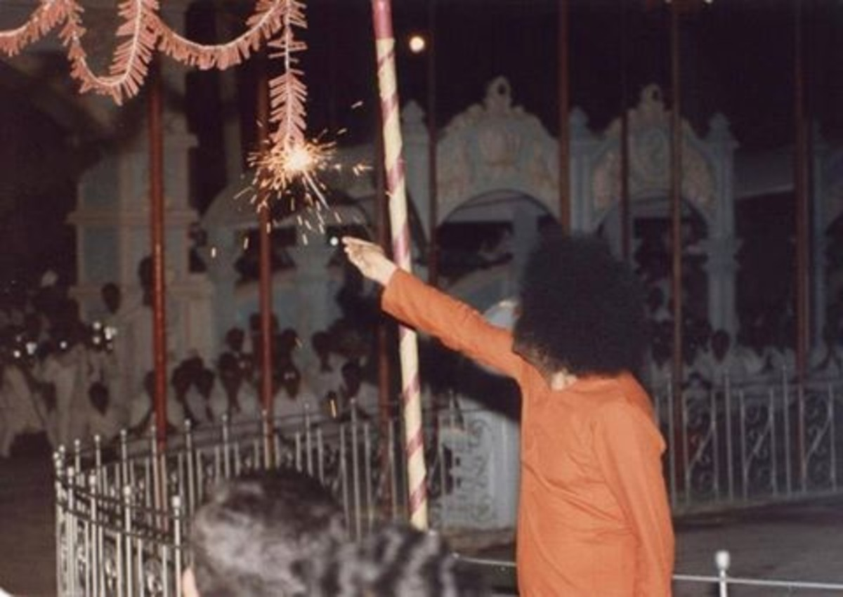 Swami lighting the 'garland crackers' in Prasanthi Nilayam.