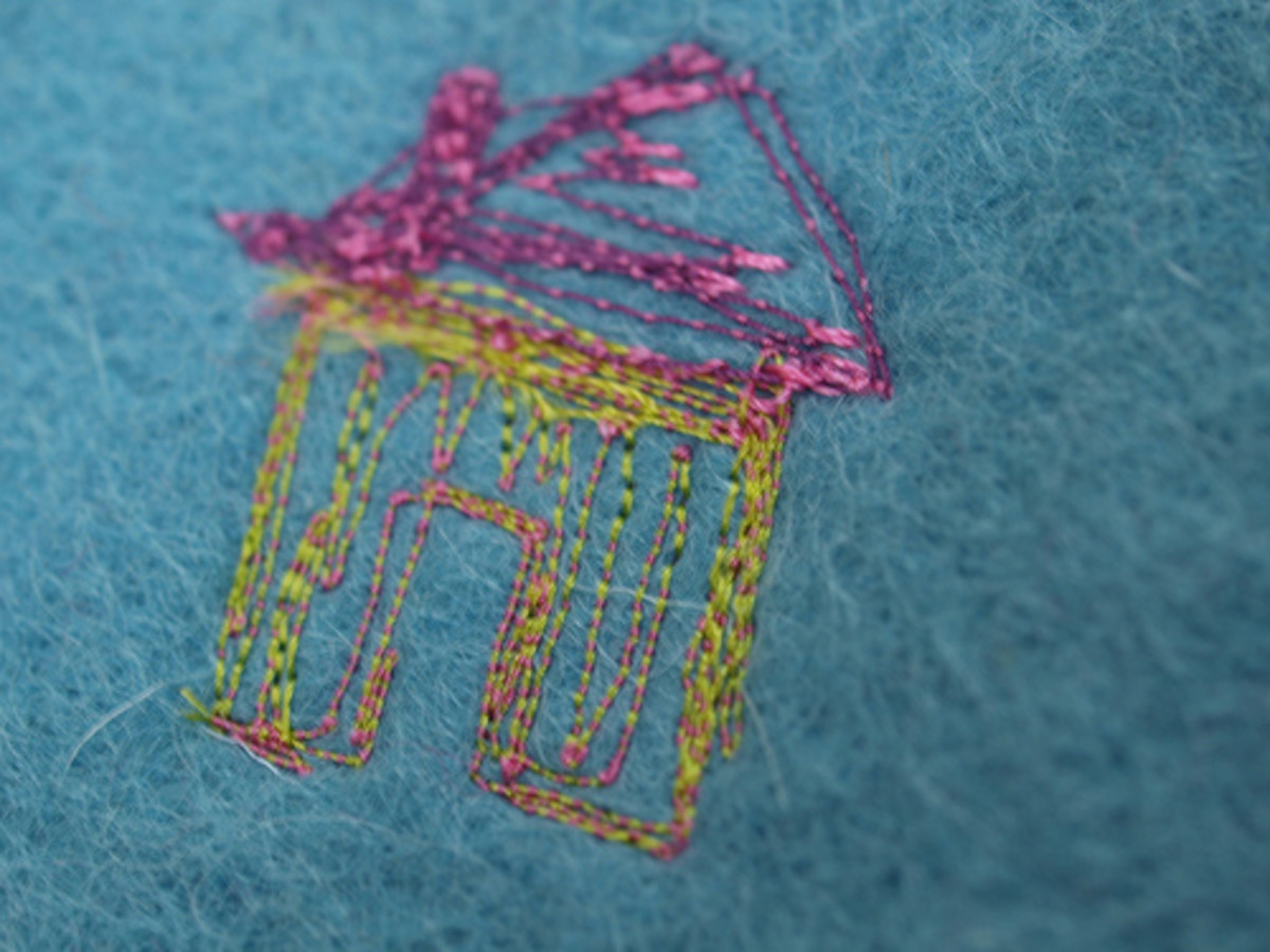 This house was created by using colored thread on a sewing machine.