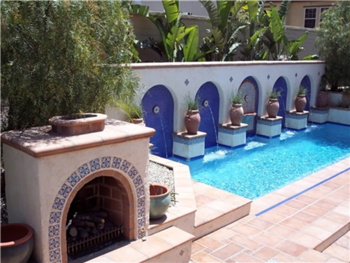 four arches blue tile walls accent the large water fountain with a tiled fireplace in the foreground