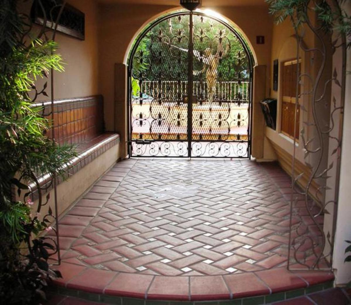 beautiful herringbone terracotta with tan porcelain tile leading to an ornate wrought iron gate and a glimpse of a water fountain with an angel just beyond the covered courtyard