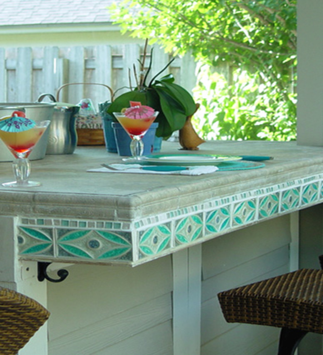 beautiful blue, teal and aqua tile edge an outdoor built in table complete with table setting and tropical drinks