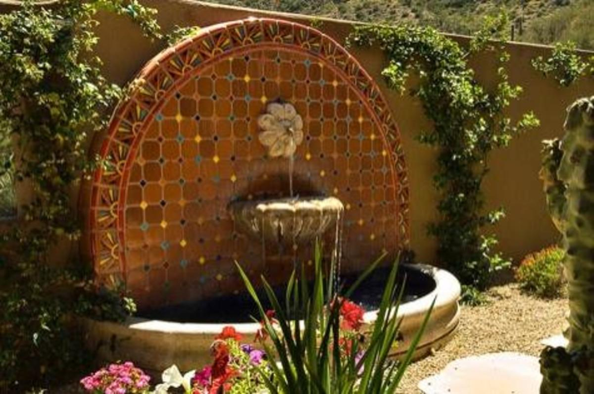 deep terracotta and tan tiles are the centerpiece for this peaceful water fountain and walled garden