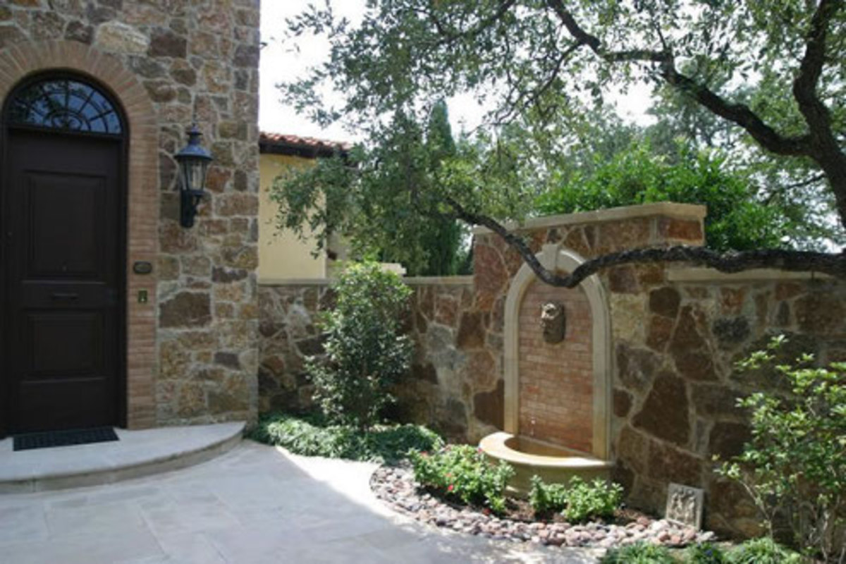 a wall decorated with a lion head and arched tile surround accent the water fountain in this beautiful garden courtyard with walled stone fence