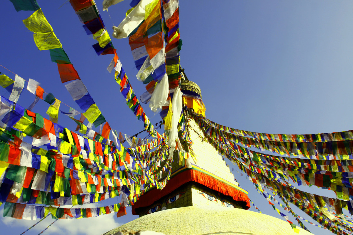 Buddhist temple with Stupa design. Prayer flags are fluttering over the white dome