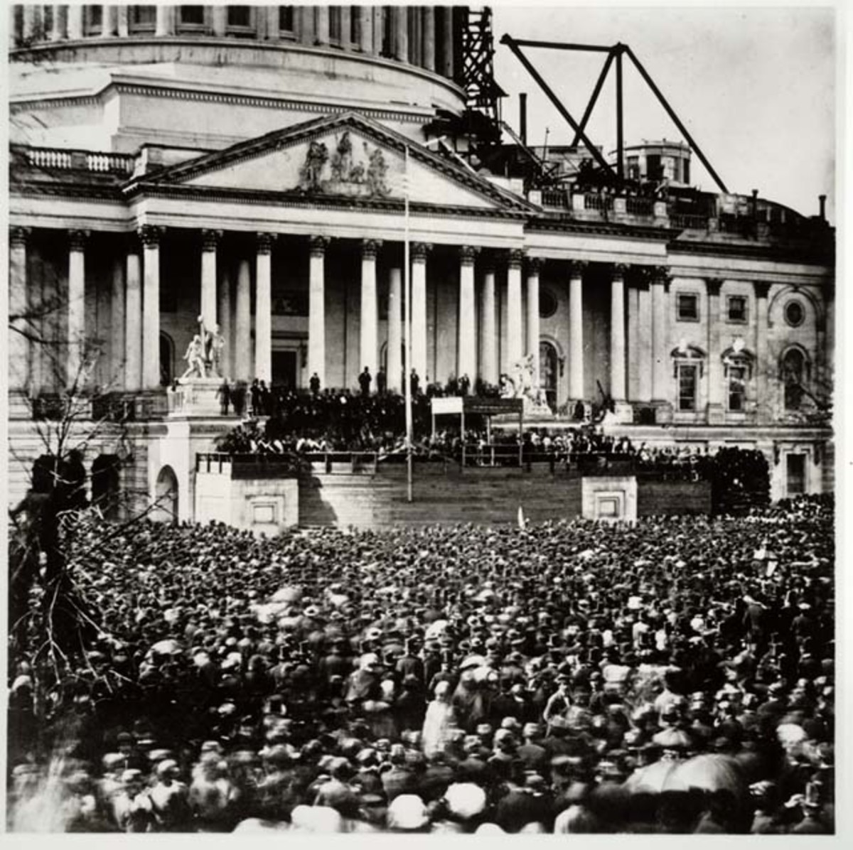 This photograph captures the crowd gathered before the east portico of the unfinished Capitol to glimpse the inaugural ceremonies.