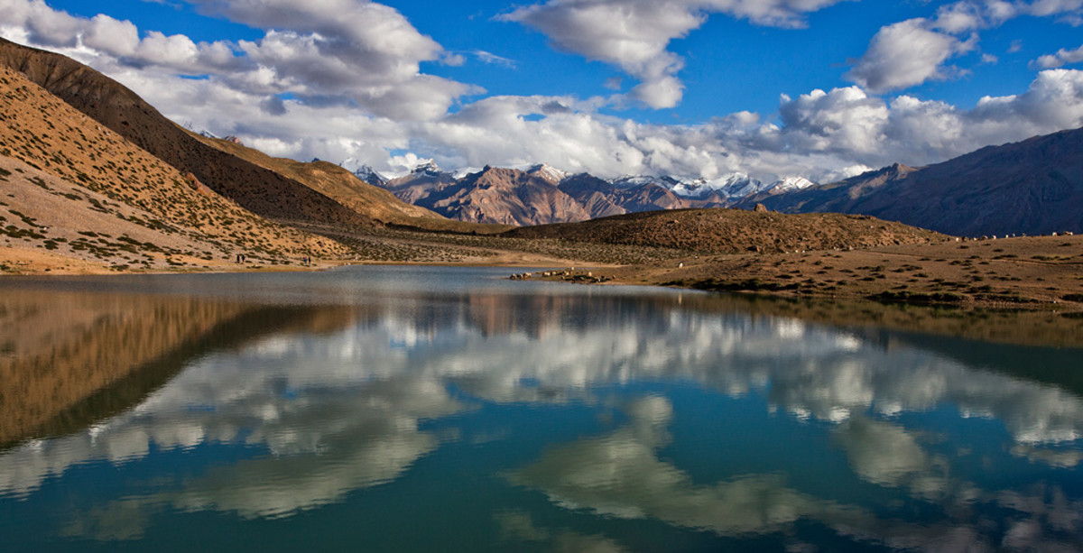 Puffy clouds reflected by the beautiful Dhankar Lake, located at an altitude of about 14000 feet in Spiti Valley, Himachal Pradesh.