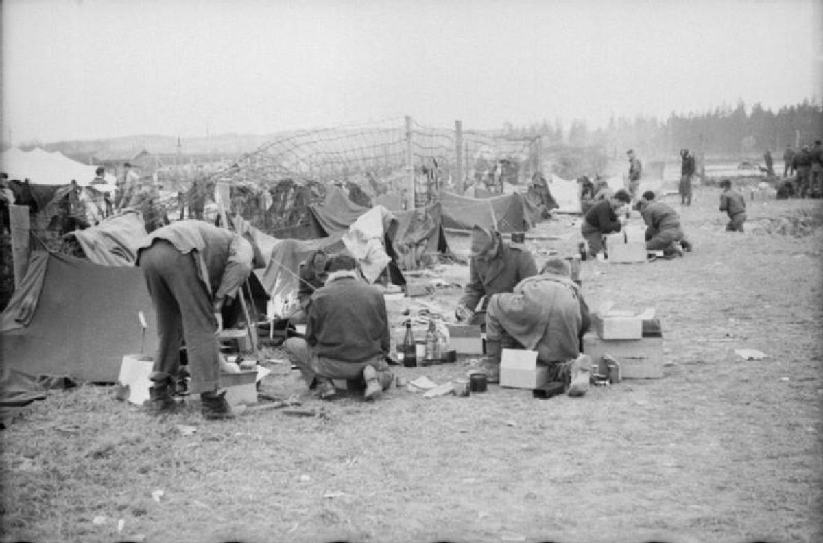 Newly liberated men from Stalag VII-A at Moosburg rummage through Red Cross parcels.