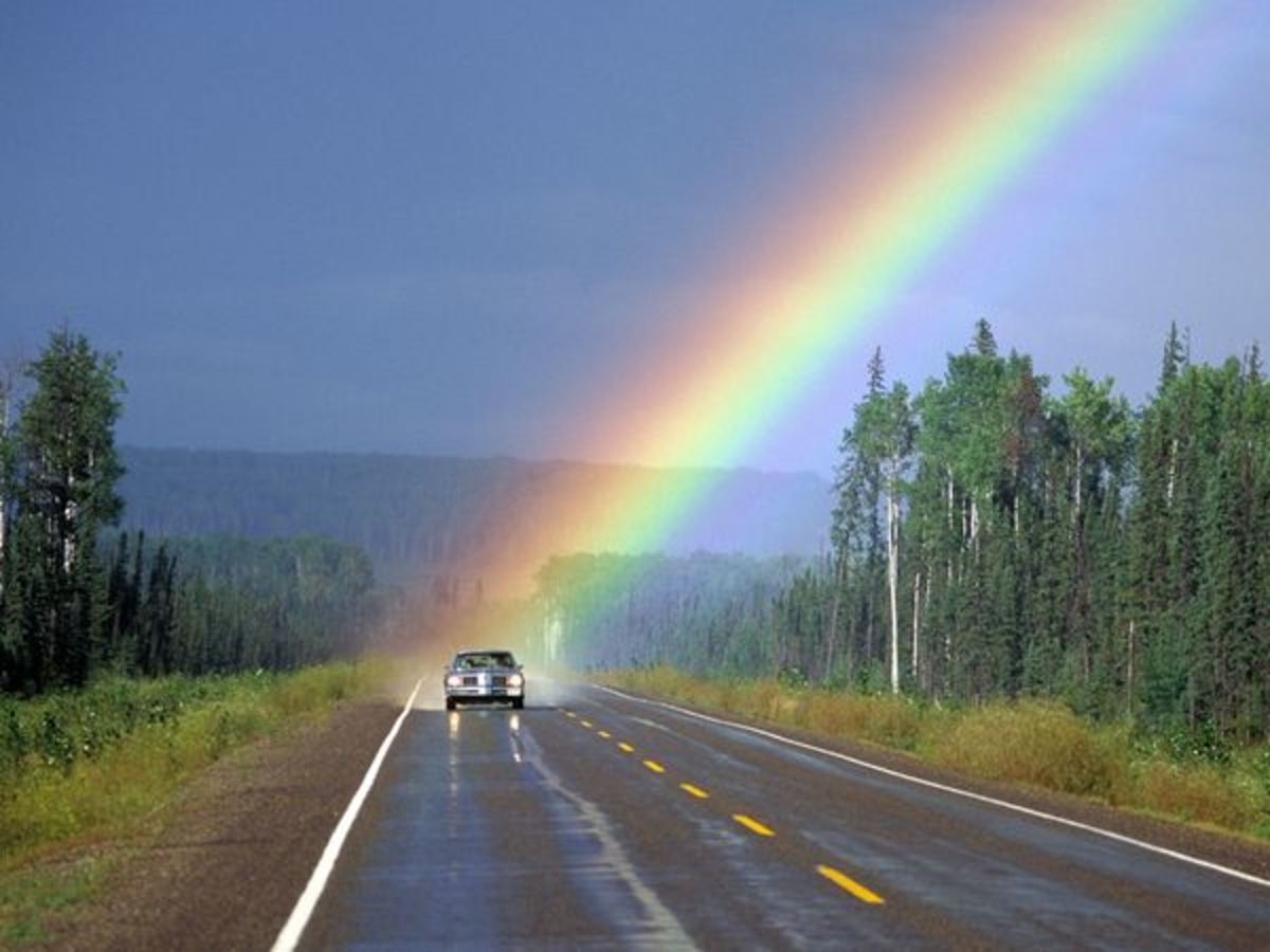 Photograph by Paul Nicklen. The end of a rainbow spotlights a solitary car traveling down a remote road in North America. http://photography.nationalgeographic.com