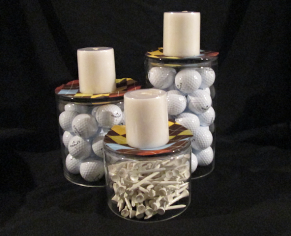 Three containers turned upside down (2 with golf balls, 1 with tees) with a plaid fabric circle and candle on top