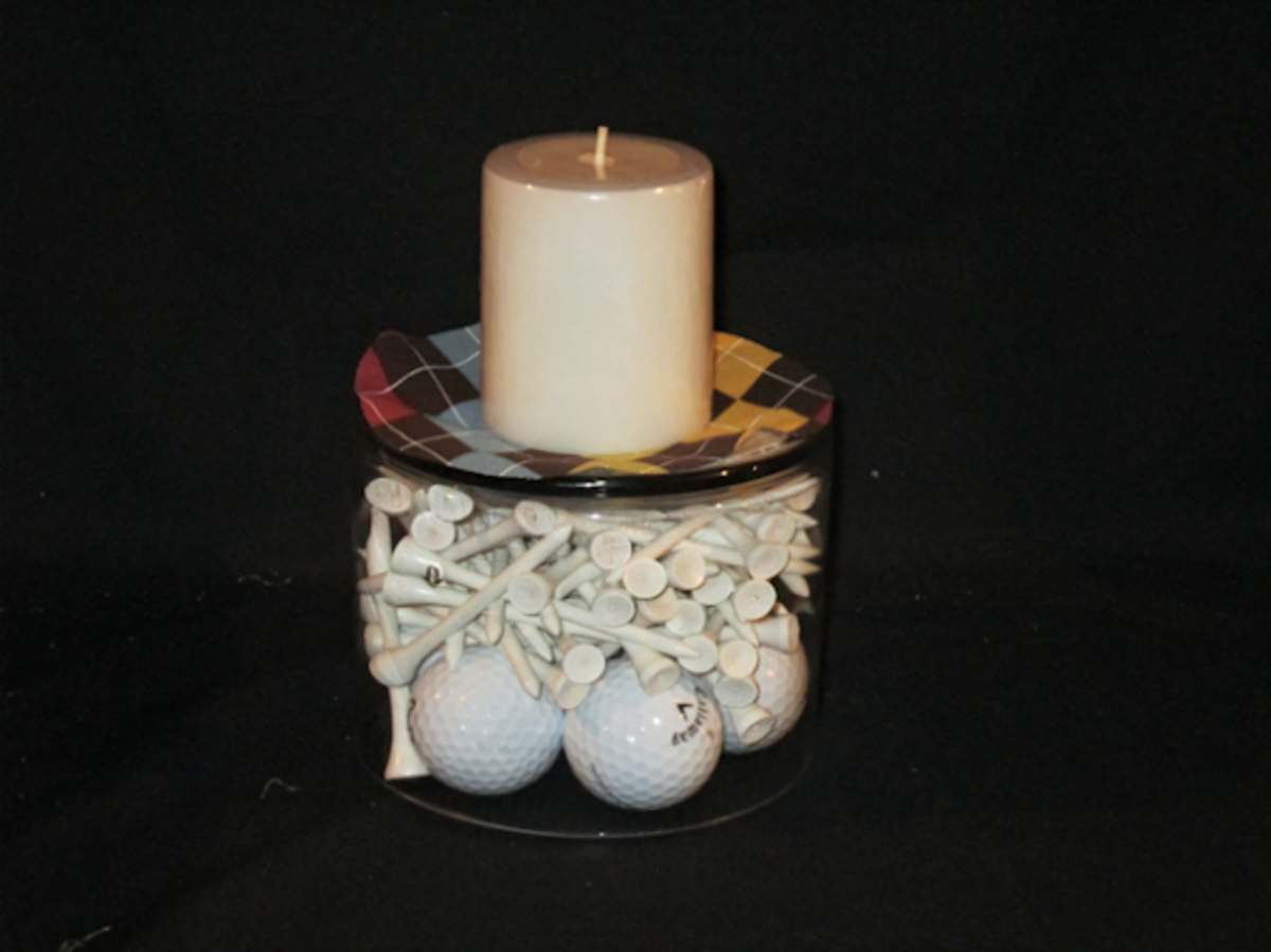 Small round container filled with tees and a few golf balls turned upside down to form a base for plaid fabric and a candle.