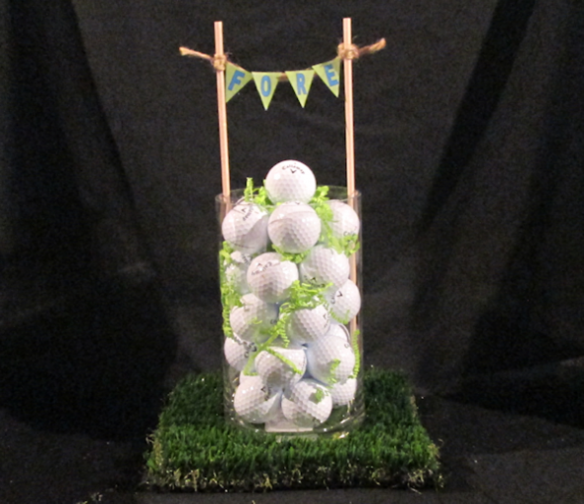 """Round vase filled with golf balls and green shred sitting atop astro-turf. Two 3/8"""" dowels and twine act as holders for the pennant flags with the word """"FORE"""""""
