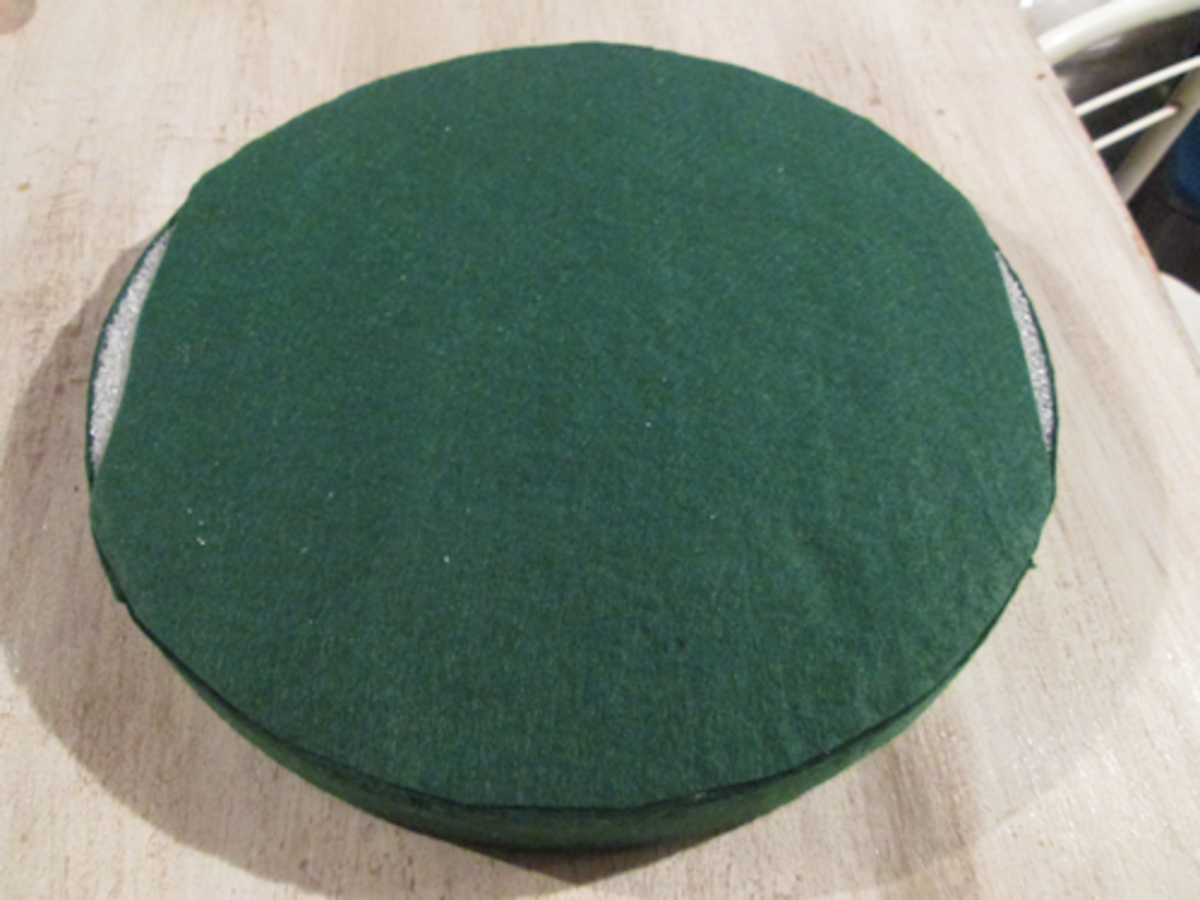 """Apply the sticky back green felt to the top of the foam circle. Now, cut out enough 1"""" pieces of the sticky felt to place on the sides of the foam circle. Peel the backing and place all your felt on the foam circle."""