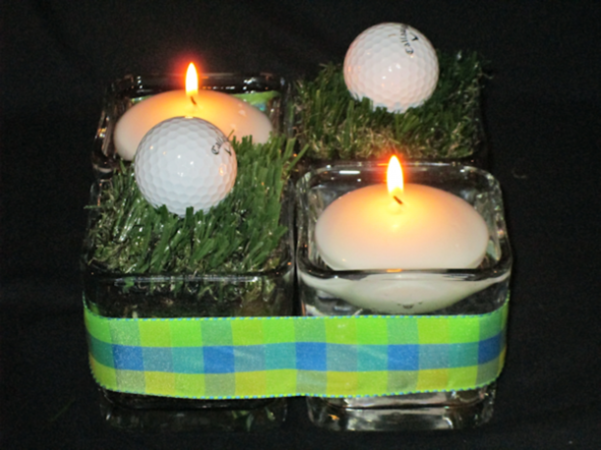 4 small, square candle holders snug up against one another to form a larger square. 2 have floating candles, two have grass with golf balls on top. A plaid ribbon is strung around the grouping.