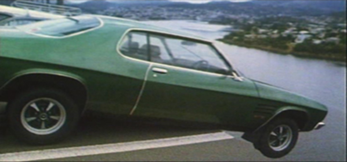 Frank Manly's two-door vehicle precariously balancing on edge of broken bridge
