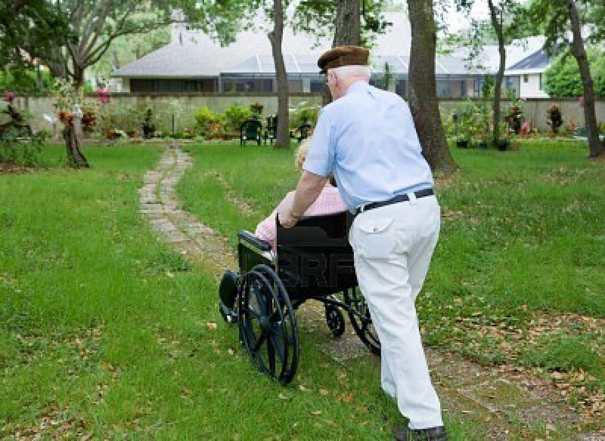 A man pushes his disabled wife as they go for a walk together