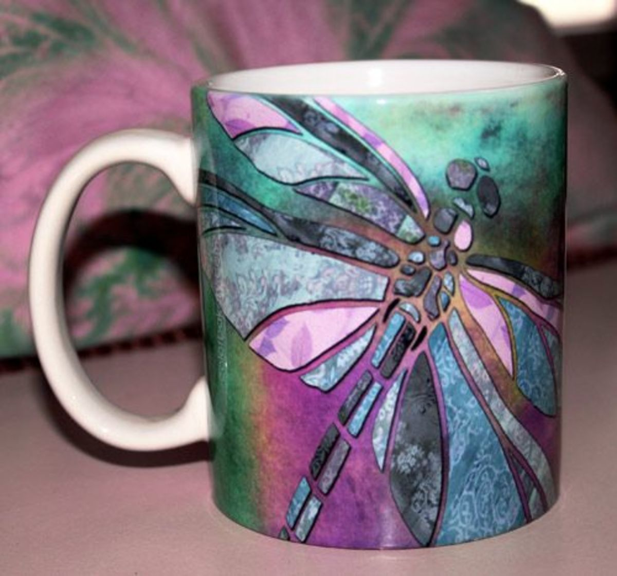 Beautiful pinks and purple and a dragonfly adorn this ceramic coffee mug