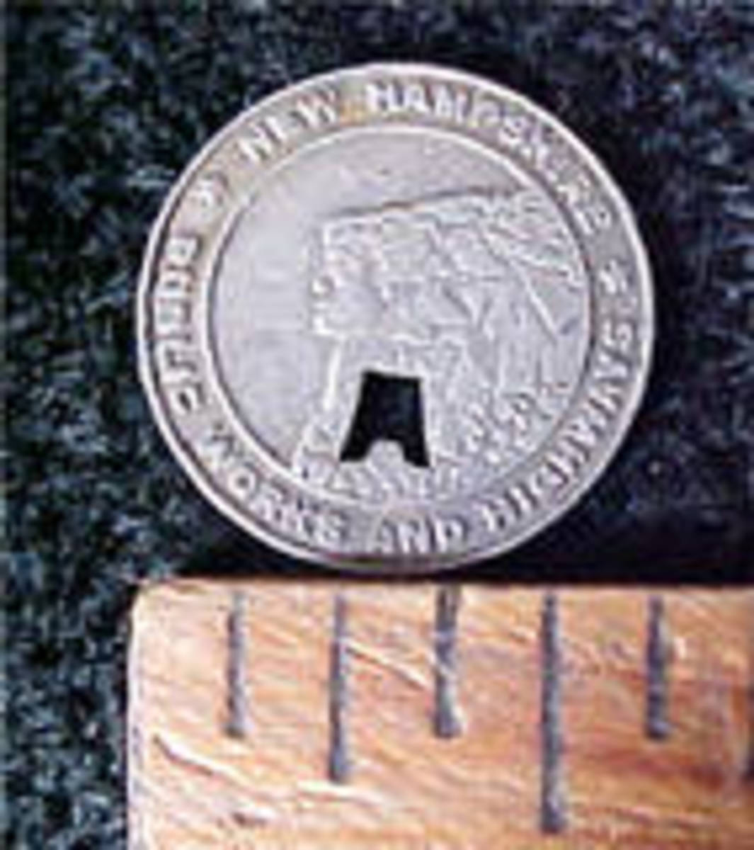 "This is an example of the New Hampshire transportation coin that shows the ""Old Man in Mountain,"" the state symbol."