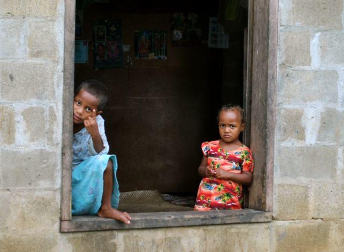 Children in a Fijian village watch us walk by
